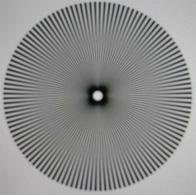 The same star segment target from figure 1.3.1 photographed from a LCD monitor and purposely defocused. Note the ring-shaped areas of minimal contrast (nodal points) , spurious resolution and contrast reversal. (after (Smith 1982))